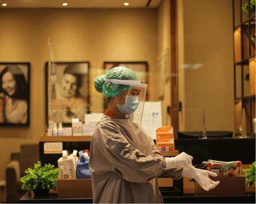 Female Doctor putting on surgical gloves wearing a full OR outfit